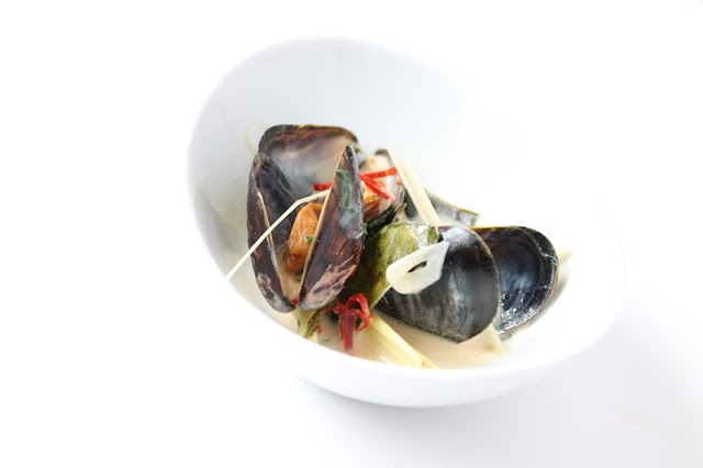 Mussels with thai flavors in a small bowl on white background