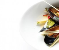Mussels with thai flavors, from above. Part of a small bowl on white background